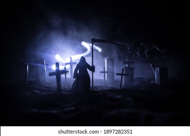 Scary view of grim reaper at cemetery with spooky cloudy sky and fog, Horror Halloween concept. Selective focus