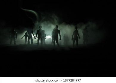 Scary view of zombies at cemetery dead tree, moon, church and spooky cloudy sky with fog, Horror Halloween concept. Selective focus