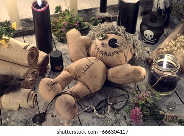 Scary voodoo doll with paper scrolls and black candles. Halloween concept. Mystic background with occult and magic objects on witch table.