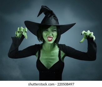 Scary witch with green skin performs magic on dark background. Halloween, horror theme.