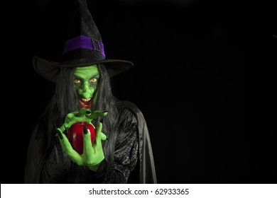 Scary witch with a poisonous apple.
