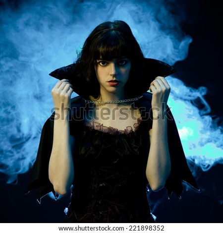 scary woman in a halloween costume with bat wings blue smoke in the background