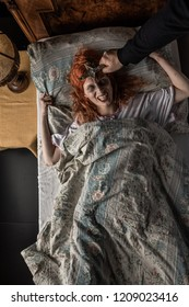 Scary woman possessed by devil in the bed. Exorcism of priest.