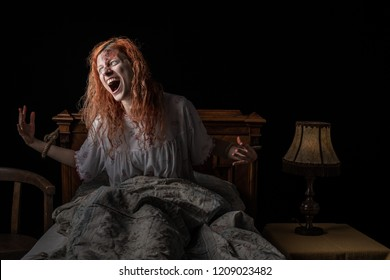 Scary woman possessed by devil in the bed. Exorcism of priest. Woman tied to the bed.