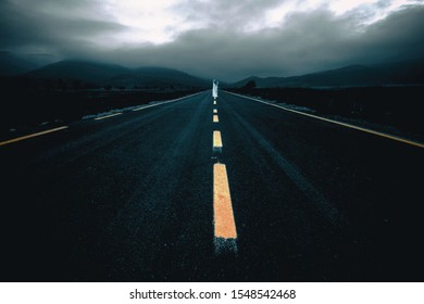 Scary Woman's Ghost at empty asphalt countryside road in twilight