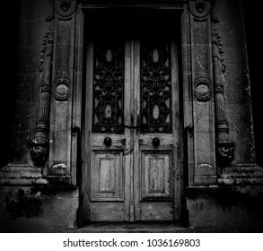 A Scary wooden Door of an Abandoned House with chains and rusted knobs in monochrome.