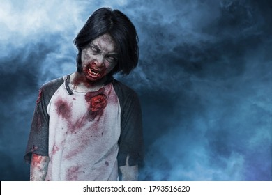 Scary zombie with blood and wound on his body standing with smog background