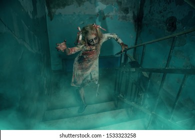 Scary zombie girl is standing on the stairs. Halloween. Horror movie.