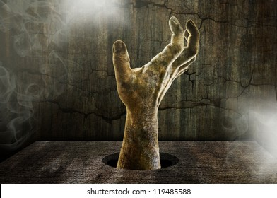 scary zombie hand coming out of a table