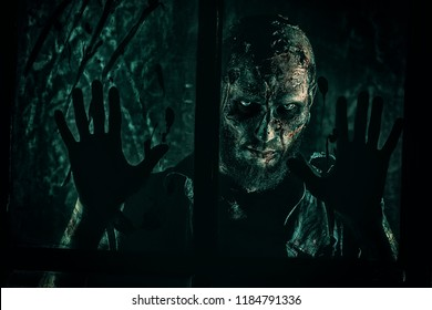 A scary zombie standing behind the window. Halloween. Horror movie.
