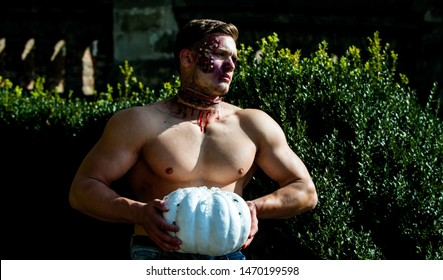 The scary zombie is in the street with pumpkin. Death - young man Halloween portrait. Halloween man with pumpkin in the street. Day of The Dead. Halloween. Strong man body. Hot guy. Fitnes
