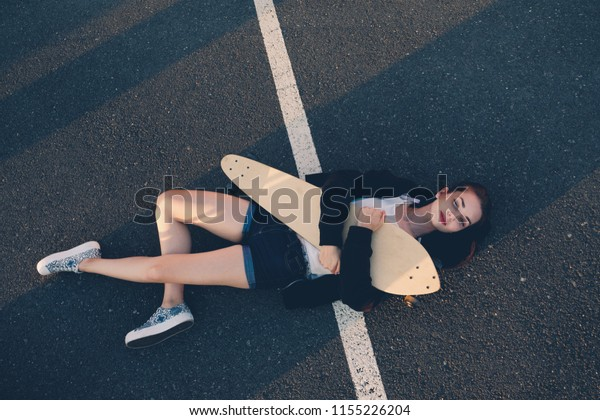 Scater Girl lying Down on asphal surface huging with her longboard