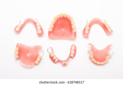 scattered acrylic dentures isolated on white background seen from above.  copy space.