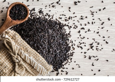 Scattered black, dried, loose tea with burlap bag and wooden spoon. Enjoying of tea break at the work, at home, at visit with friends, family or alone everyday. Classic warm or hot drink. Top view.