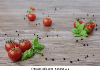 Scattered cherry tomatoes wwith pepper and leaves of basil on the wooden, brown table with the light wooden board. .