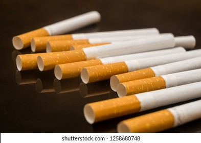scattered cigarettes on the black glass table