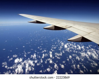 Scattered Cloud pattern with Airplane wing over ocean