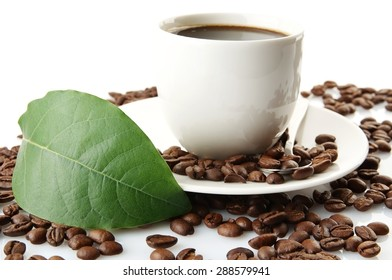 Scattered coffee beans with cups of coffee and green coffee leaf