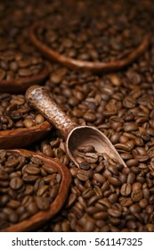 scattered coffee beans with a little wooden scoop on a dark background