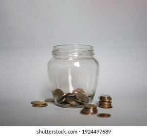 Scattered coins lie near a jar with money