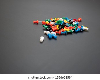 Scattered colorful push pins on a dark slate background. School and office supplies.