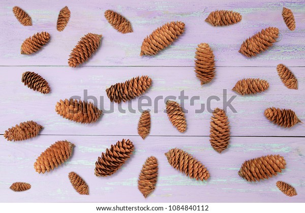 Scattered cones on purple wooden background. View from above