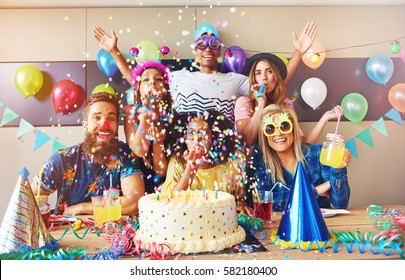 Scattered confetti falling around group at party with birthday cake and cone hats on table in foreground