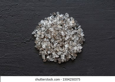 Scattered diamonds on a black background. Raw diamonds and mining, a scattering of natural diamond stones. Graphite quartz. Natural stones and minerals. A mountain or a pile of stones. Copy space.