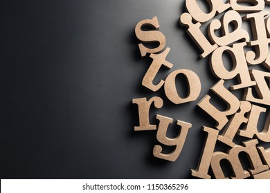 Scattered English letters with STORY word on black plastic background
