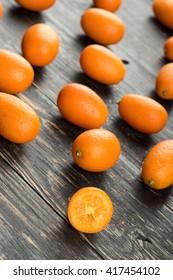 Scattered fresh fruit kumquat on the wooden background