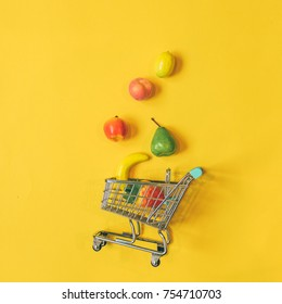 the scattered fruits from the grocery carts on yellow background.