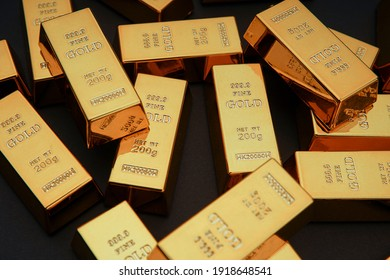Scattered gold bars on the black table. Shiny precious metals for investments or reserves. Bank image and photo.