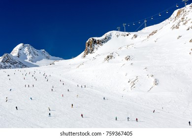 Scattered groups of skiers descend a wide ski run at the Tiefenbach glacier at the Austrian ski resort Soelden.