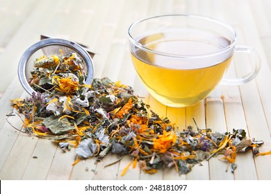 Scattered herb on bamboo in ball strainer and transparent cup with yellow herbal tea