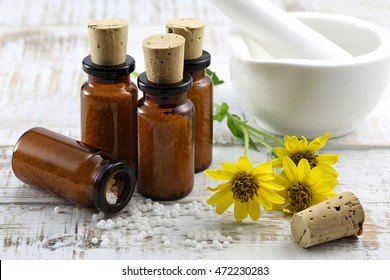 scattered homeopathic arnica pills on wooden background
