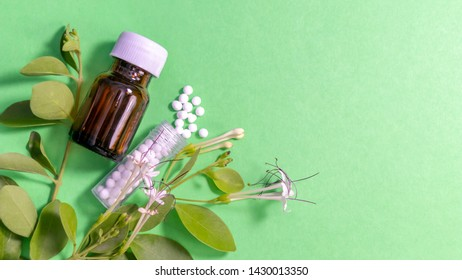 Scattered Homeopathic remedy and a glass bottle with leaves on green background