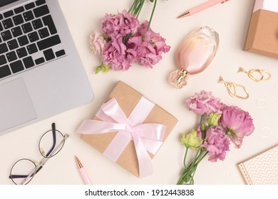 Scattered laptop, gifts, flowers and feminine accessories on a beige background. Online celebrate or shopping concept.