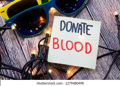 Scattered Lighted Tiny LED Stringlight on Wooden Surface. Two Colorful Sunglasses with Light Reflecting. Handwritten Message on Voluntary Blood Donating.