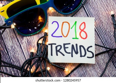 Scattered Lighted Tiny LED Stringlight on Wooden Surface. Two Colorful Sunglasses with Light Reflecting. Handwritten Message on Year 2018 Innovating Trend
