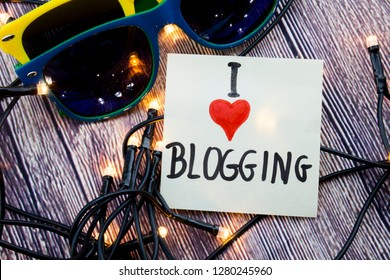 Scattered Lighted Tiny LED Stringlight on Wooden Surface. Two Colorful Sunglasses with Light Reflecting. Blogger Expressing Love of Writing on White Paper.
