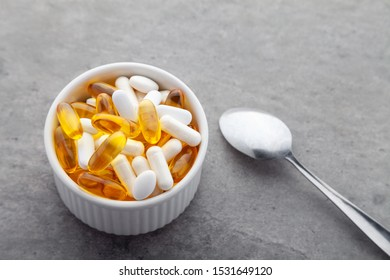 Scattered medicine vitamins, pills, drugs in bowl with metal spoon on gray background. White food dietary supplement hard shelled capsules filled with powder, salmon oil softgel Omega 3