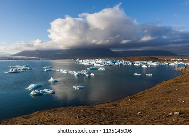 Scattered melting icebergs near Jokulsarlon glacier lagoon shore. Global warming and climate change concept with melting ice. Base of the Vatnajokull glacier at Jokulsarlon, Iceland.