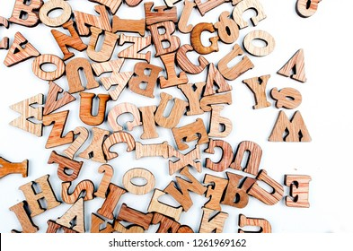 scattered mixed brown wooden letters of the English alphabet on white background, copy space, as a background composition
