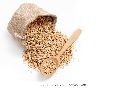 Scattered oat flakes in wooden spoon and sack on white background. Top view, high resolution product