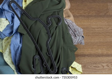 scattered on the floor clothes and clothes hangers, the concept has nothing to wear