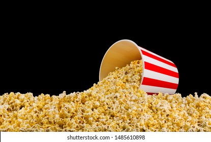 Scattered popcorn from paper striped bucket isolated on black background, concept of watching TV or cinema.