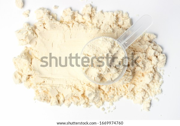 Scattered protein and measuring spoon on white background top view, concert of sports nutrition.