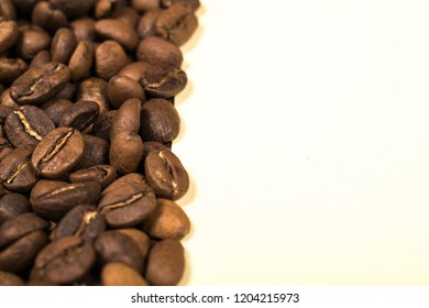 Scattered roasted coffee beans on beige background. Close up. Copy space.