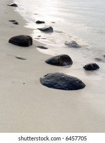 Scattered rocks embedded in the sand on a beach as the low setting sun is reflected off the breaking surf of the sea.