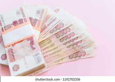 Scattered ruble currency banknotes, closeup view.Russian rubles, five thousand bill isolated on pink background.Money. Russian ruble.Falling ruble, still life with financial charts